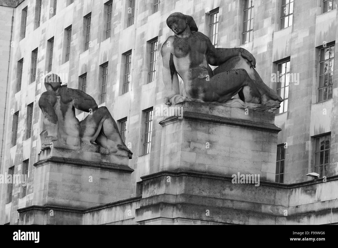 Two stone sculptures at the entrance to the Ministry of Defence building in Whitehall, London, England. - Stock Image