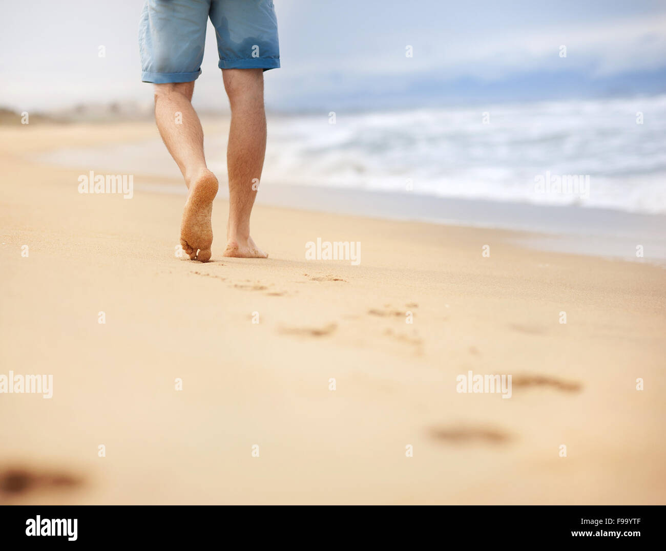 Detail of male feet walking at the sandy beach - Stock Image