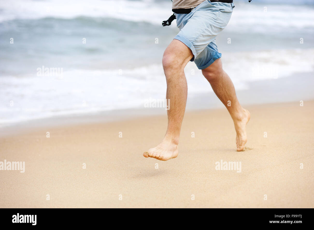 Detail of male feet running at the sandy beach Stock Photo