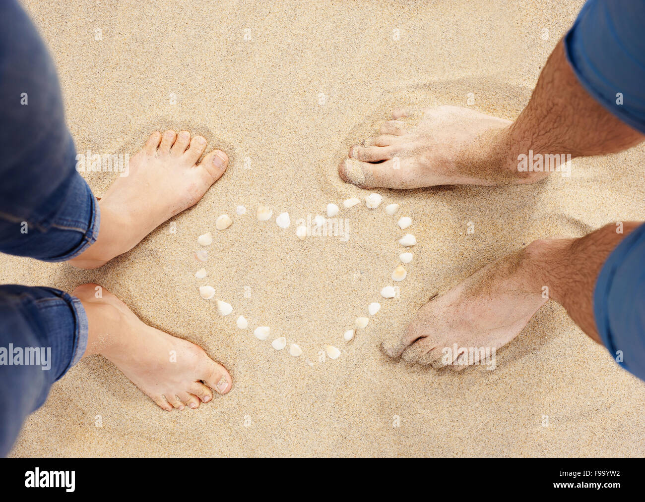 Female And Male Feet Closeup Of Woman And Man Standing Next To The S Heart At The Sandy Beach