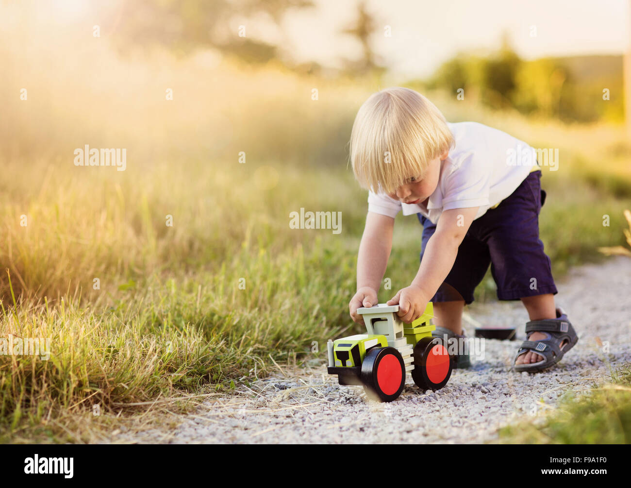 Little boy playing with toy tractor on countryside road Stock Photo