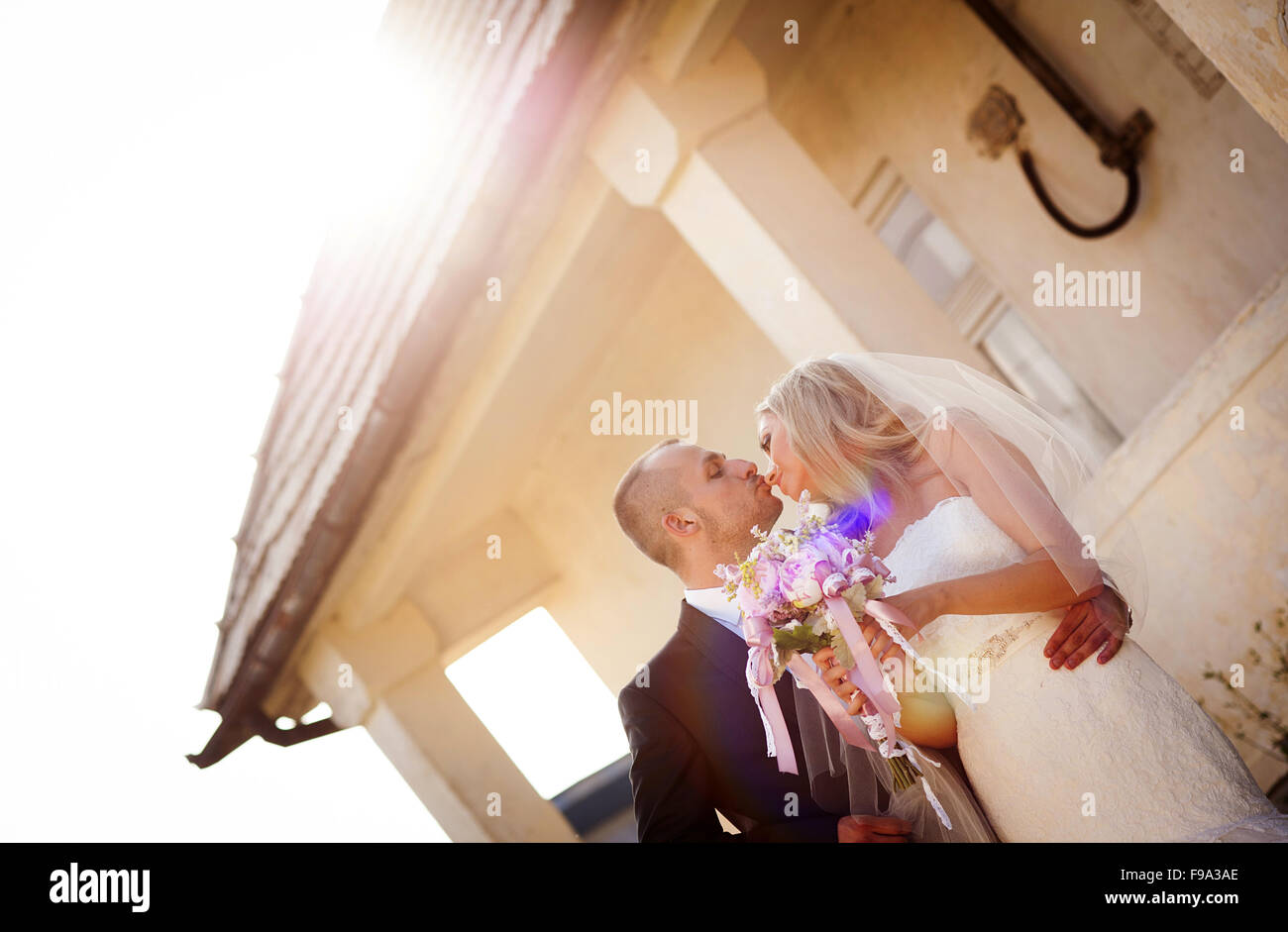 Happy bride and groom posing by the old house - Stock Image