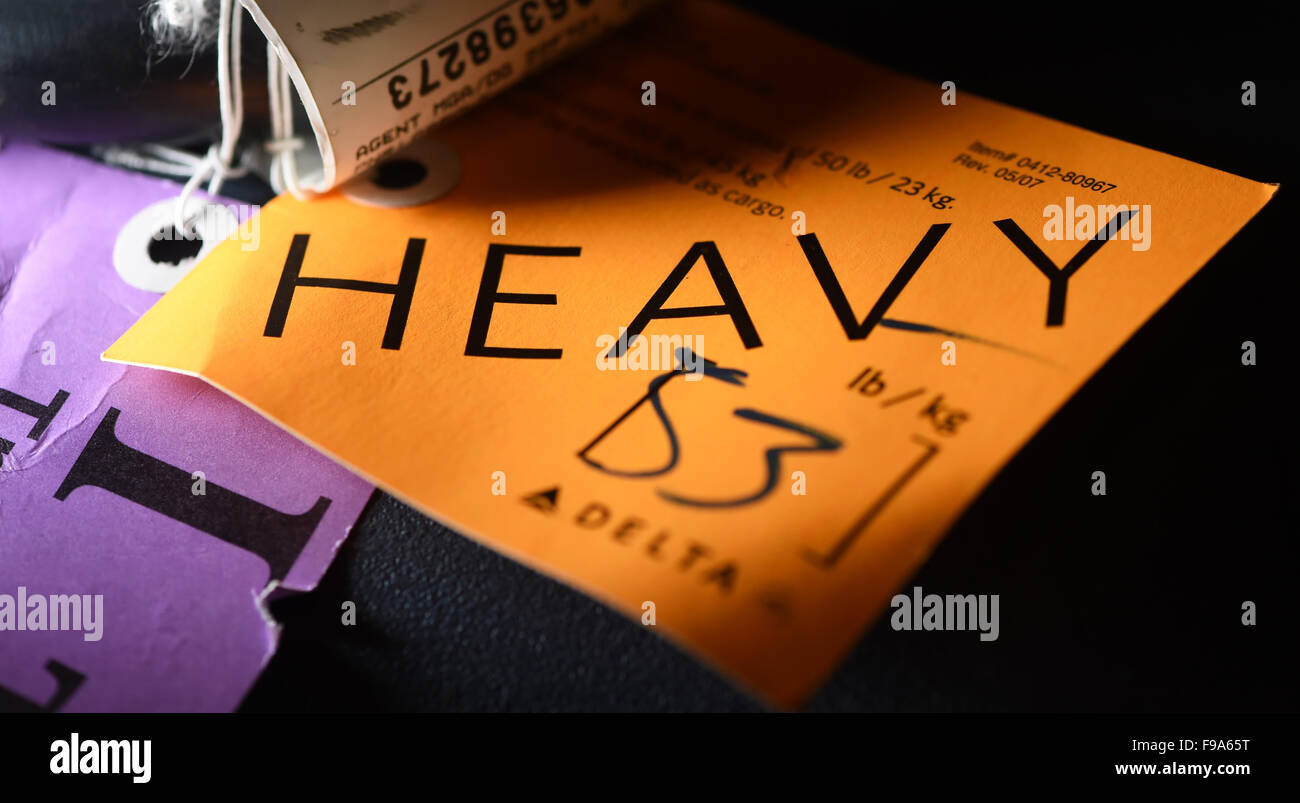 Berlin, Germany. 07th Dec, 2015. A luggage tag of an airline reads 'heavy' for excess baggage in Berlin, - Stock Image
