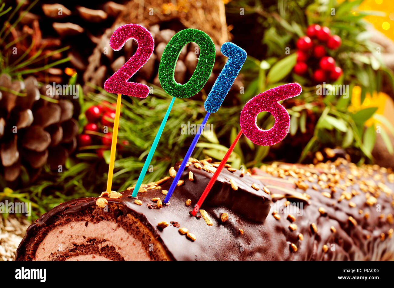 a yule log cake, traditional of christmas time, topped with glittering numbers of different colors forming the number - Stock Image