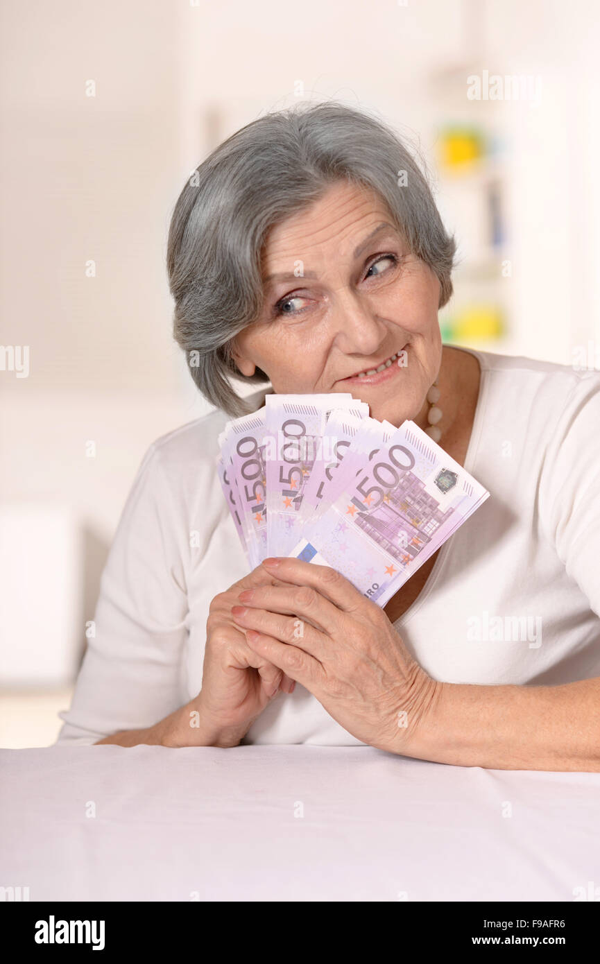 Aged woman holding euros Stock Photo