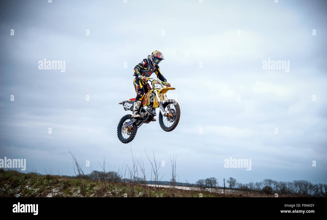 Motocross motorcycle action, off-road dirt track image, during late winter. - Stock Image