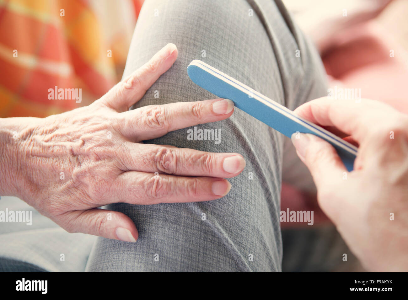 closeup of an older woman's hand with nailfile - Stock Image