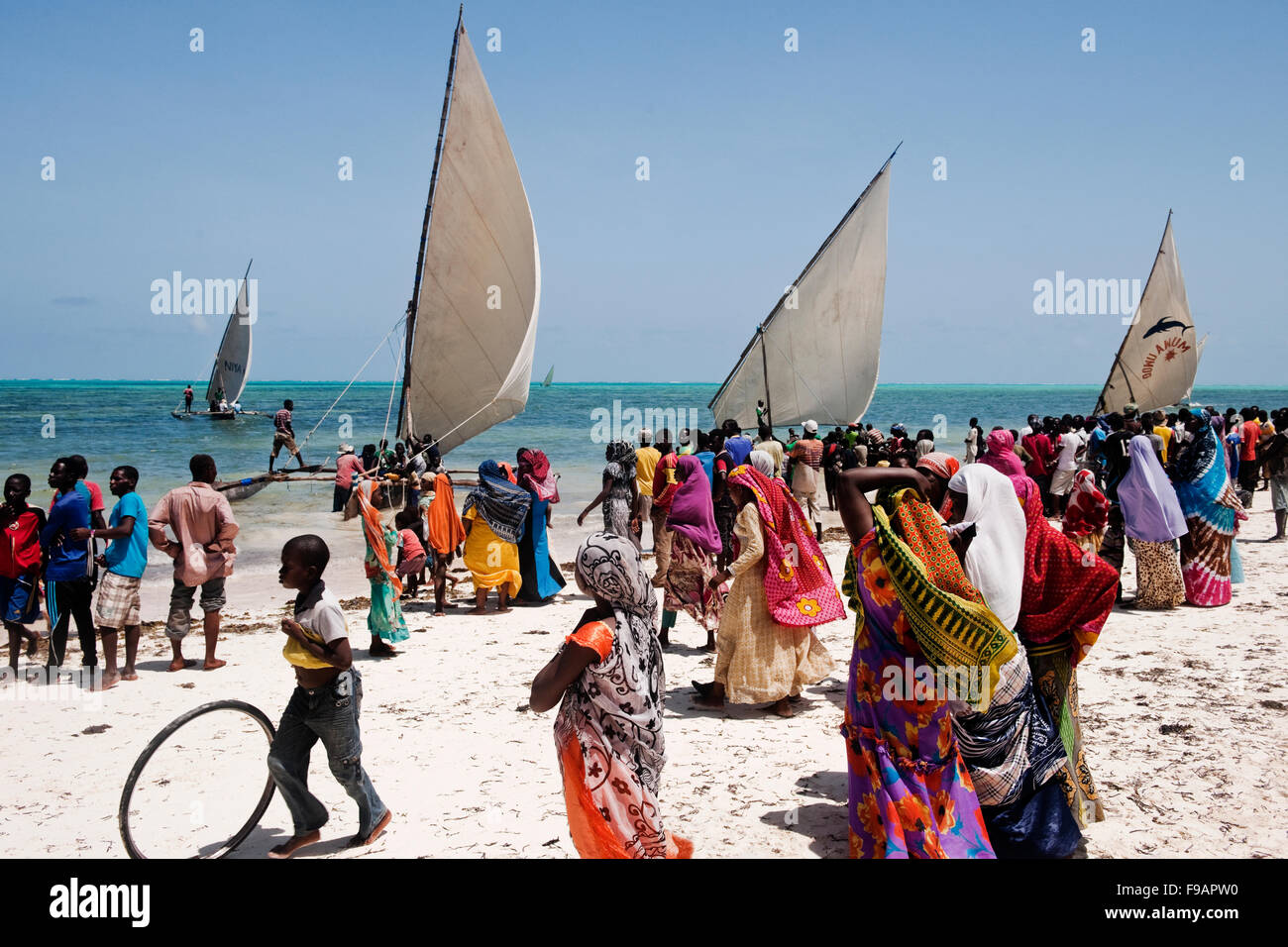 Villagers in colorful clothes from the village of Jambiani in Zanzibar gather to watch the annual Dhow race - Stock Image