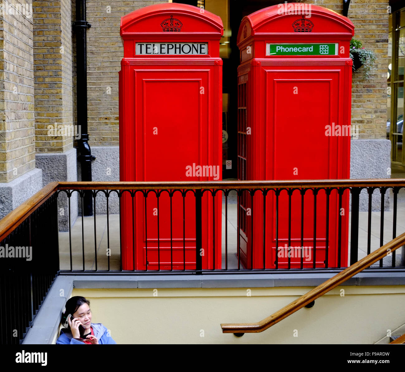 Street photography in London - advancing technology, woman on a mobile phone, in front of 2 telephone boxes - Stock Image