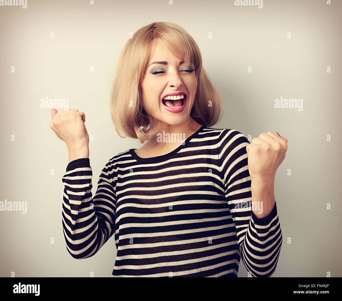 Happy excited winner with opened mouth. Happy blond young satisfaction woman showing the gesture by fists. Vintage - Stock Image