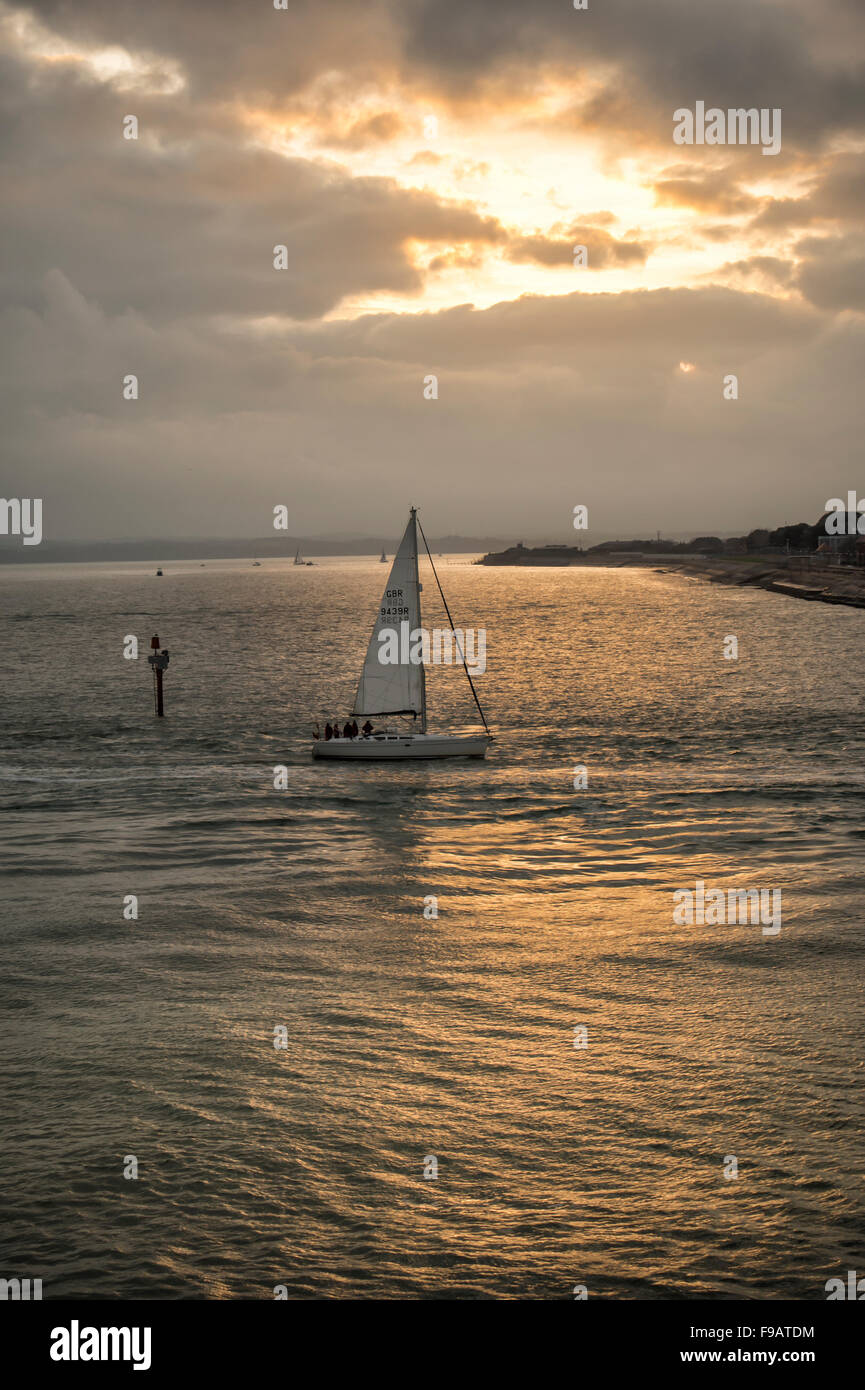 sailing boat returning to port at dusk - Stock Image