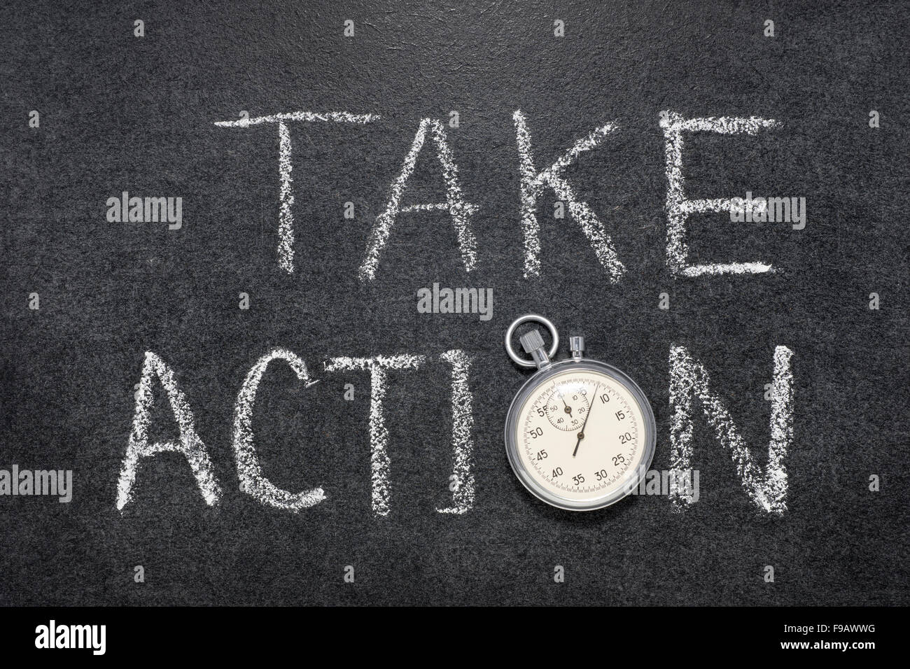 take action phrase handwritten on chalkboard with vintage precise stopwatch used instead of O - Stock Image