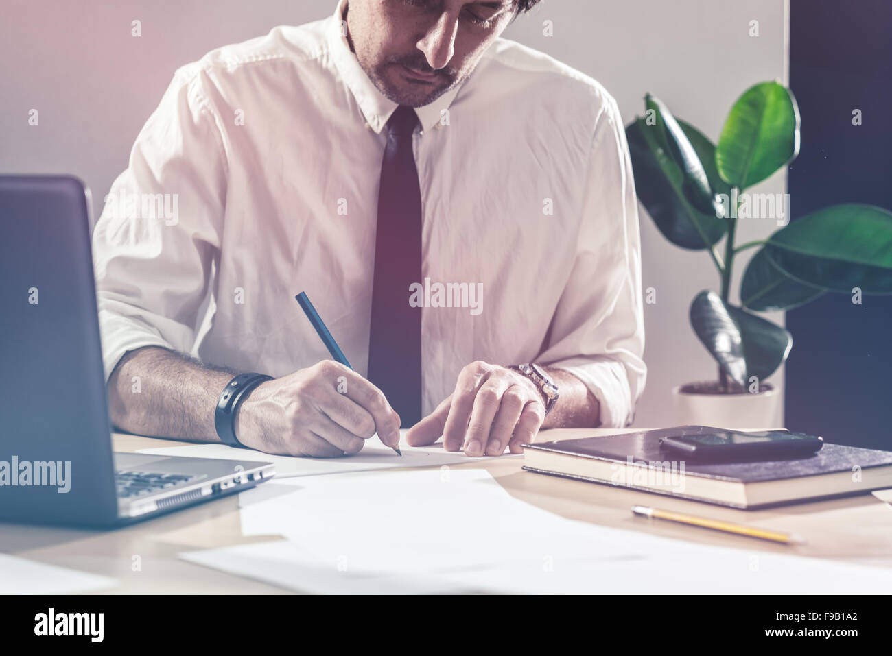 Businessman sketching business diagram, working overtime at office desk, multitasking and project deadline concept, - Stock Image