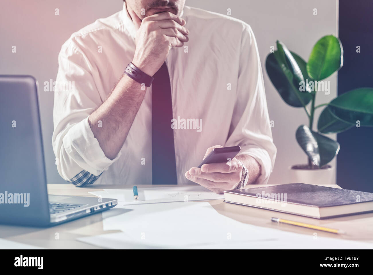 Businessman using mobile phone, working overtime at office desk, multitasking and project deadline concept, retro - Stock Image