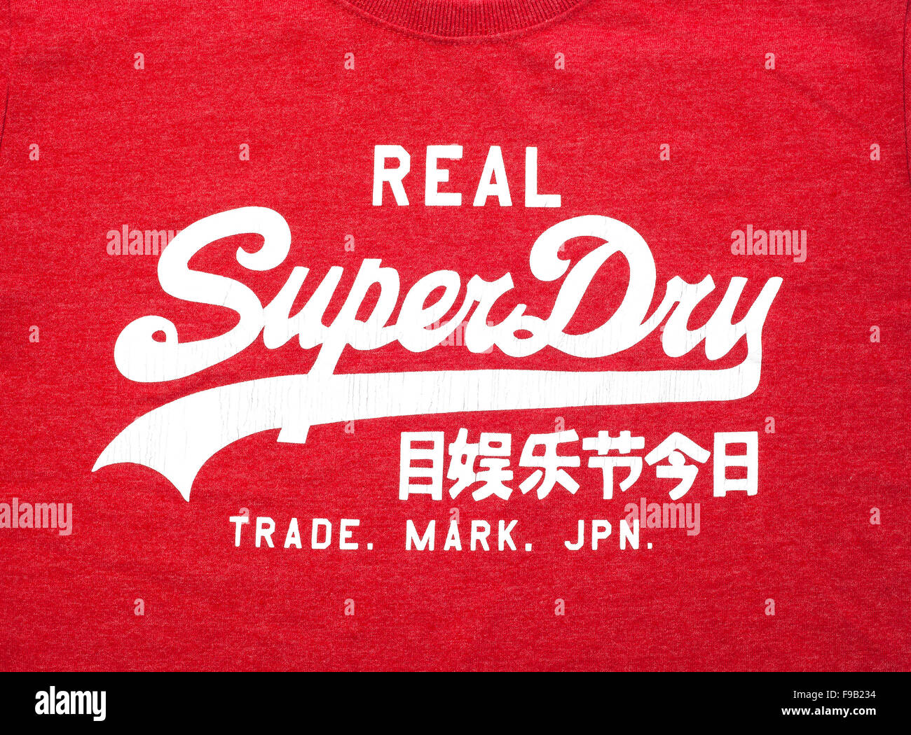 A Red Superdry Tee Shirt showing the Logo on a white background - Stock Image