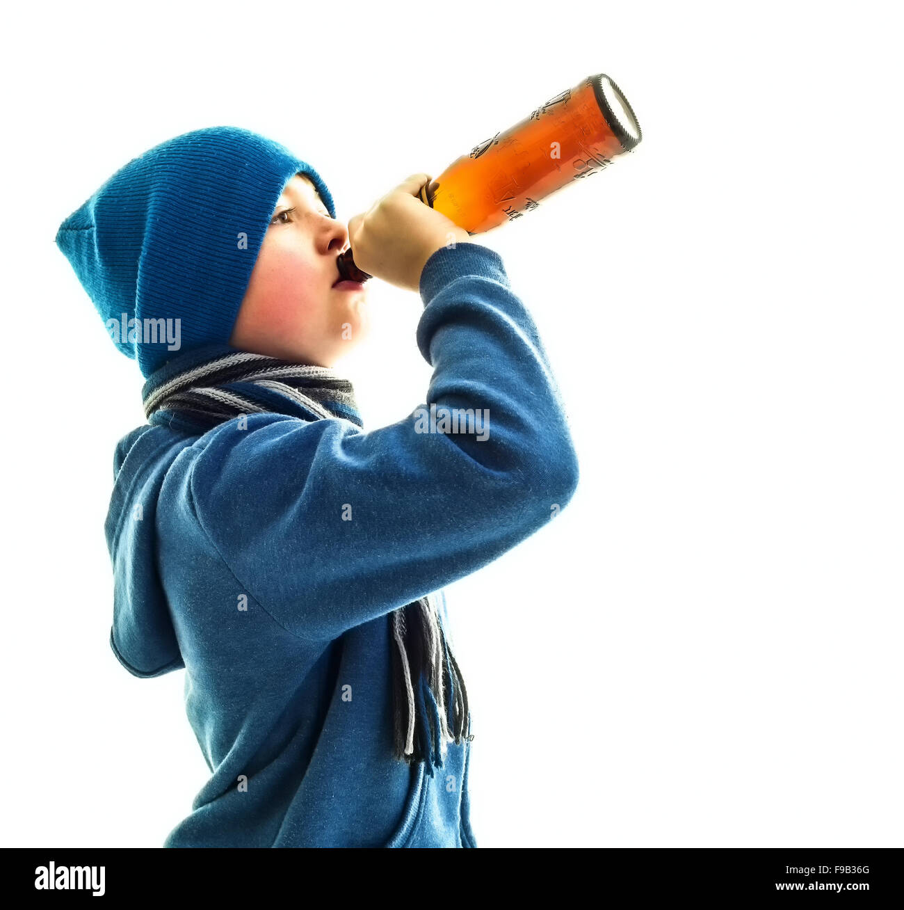 Underage Drinking Young Underage Boy Drinks Beer From Bottle, Youth social issues concept - Stock Image
