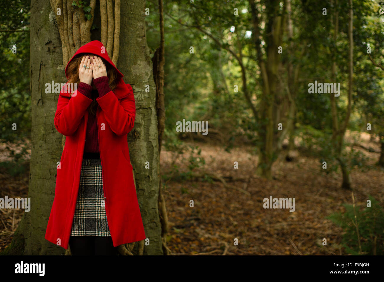 A young woman alone in woodland wearing a 'red riding hood' coat, covering her eyes, playing hide and seek, - Stock Image