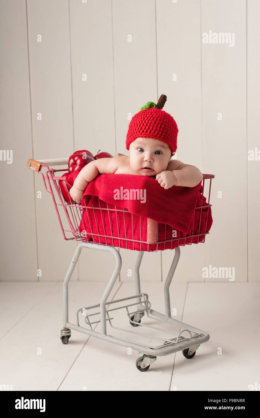 A four month old baby girl wearing a crocheted, apple hat. She is sitting in a little, vintage shopping cart. - Stock Image