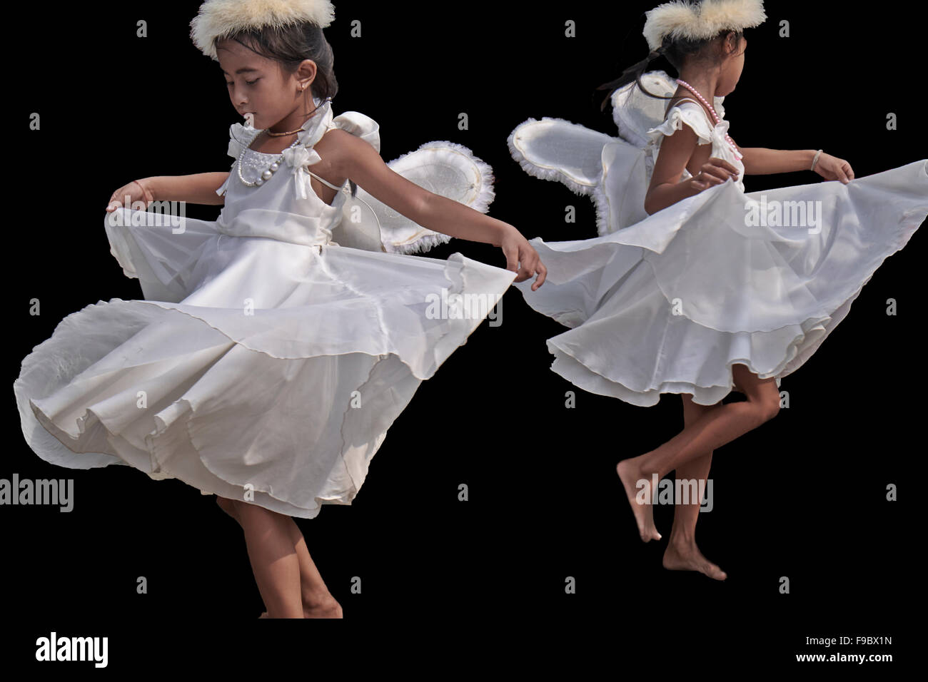 Young Thai girls, dressed as Angels, twirling and spinning as part of their dance routine. - Stock Image