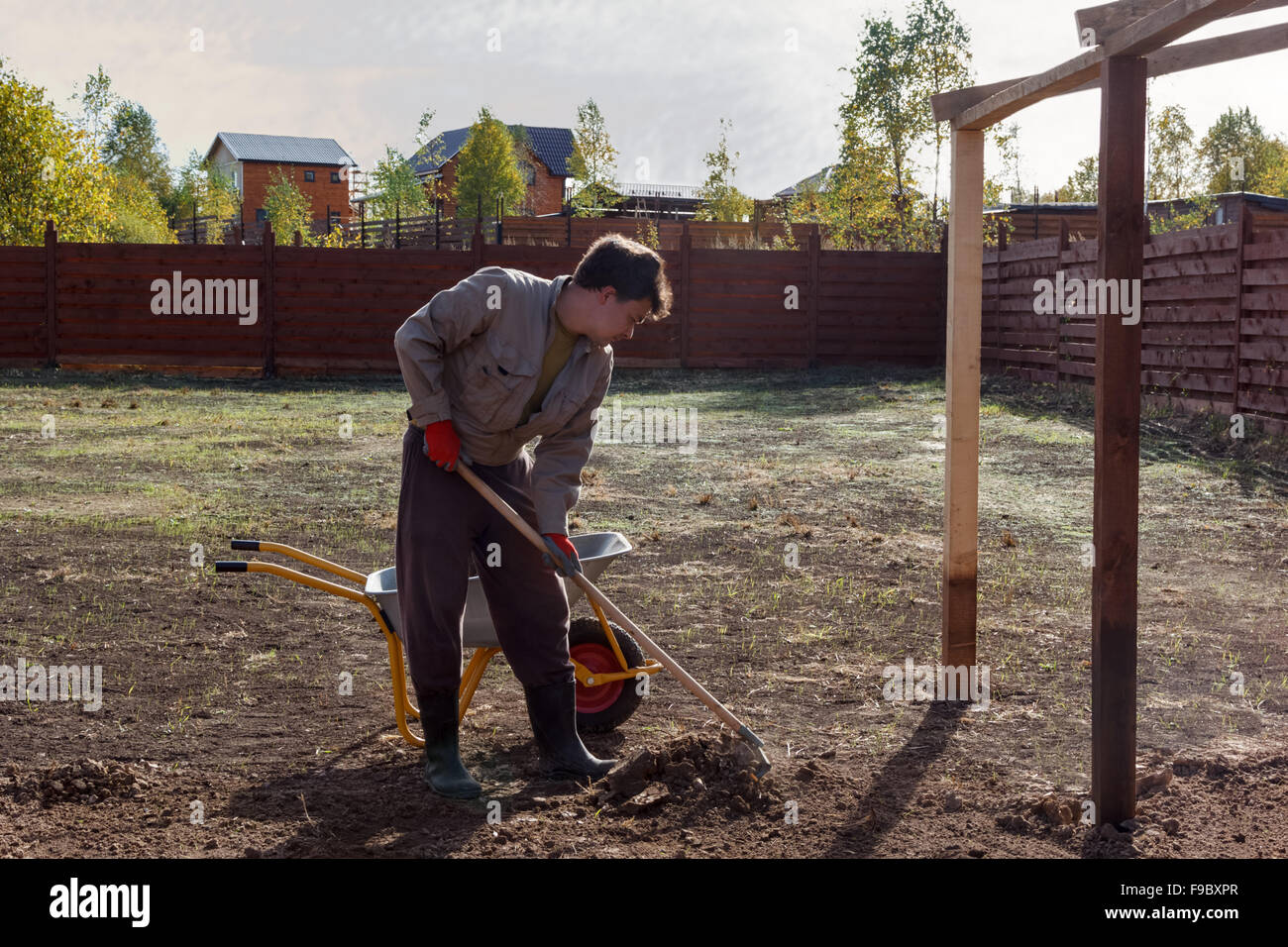 man leveles the ground with a rake - Stock Image