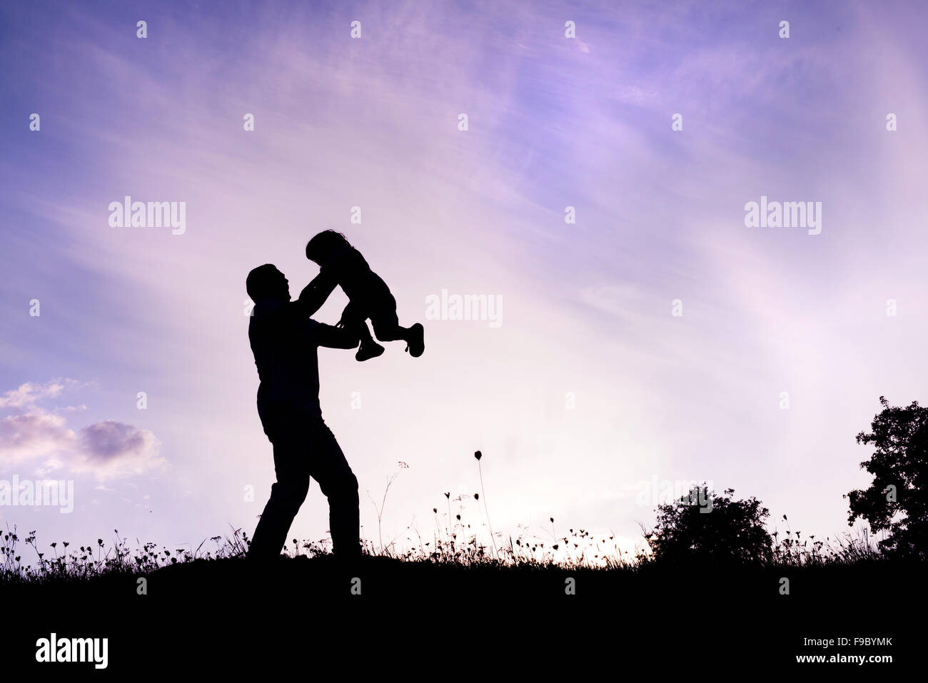 Silhouette of happy father having fun with his son - Stock Image