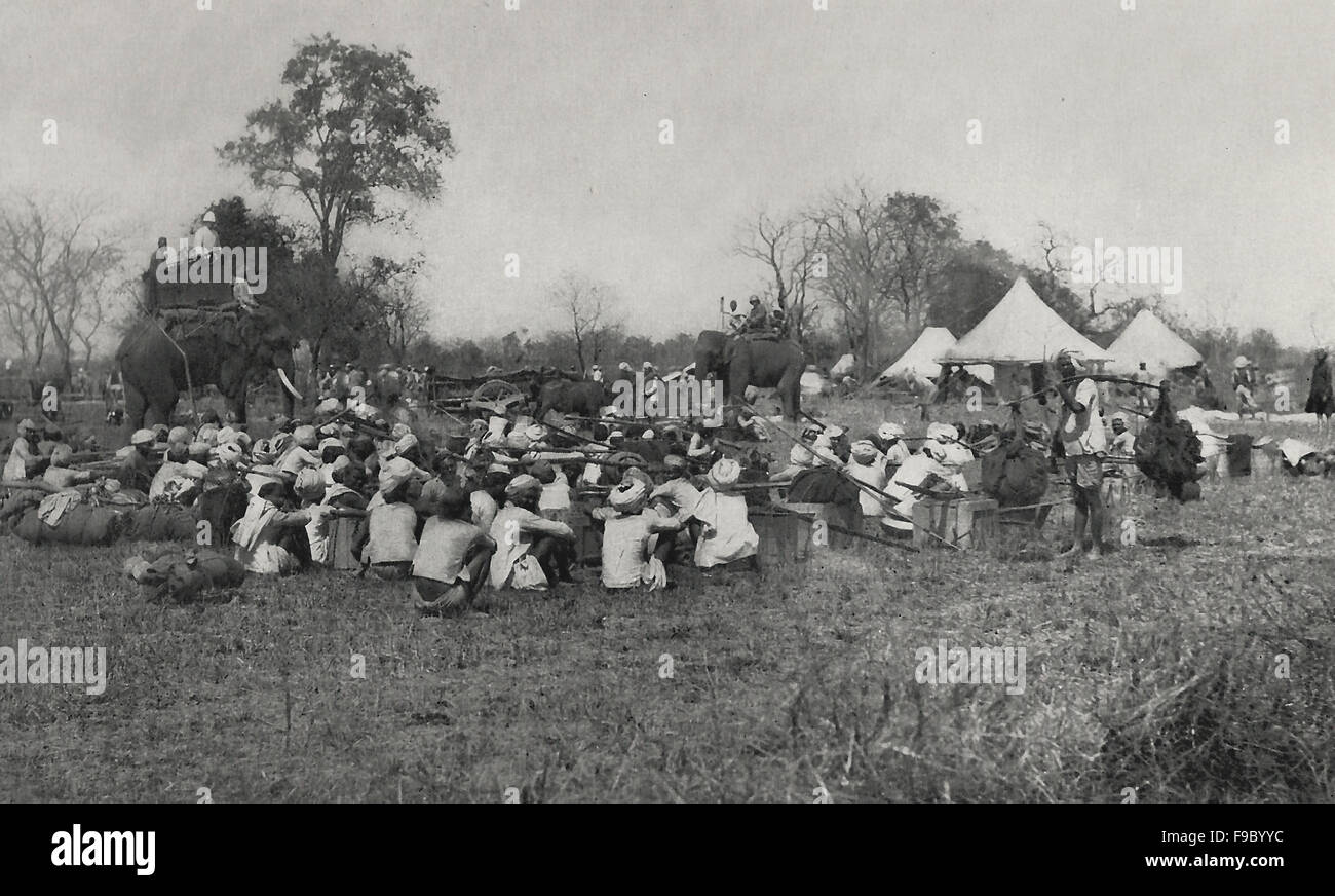 Luxurious Hunting in India - The camp of a large party, with porters in the foreground - Stock Image