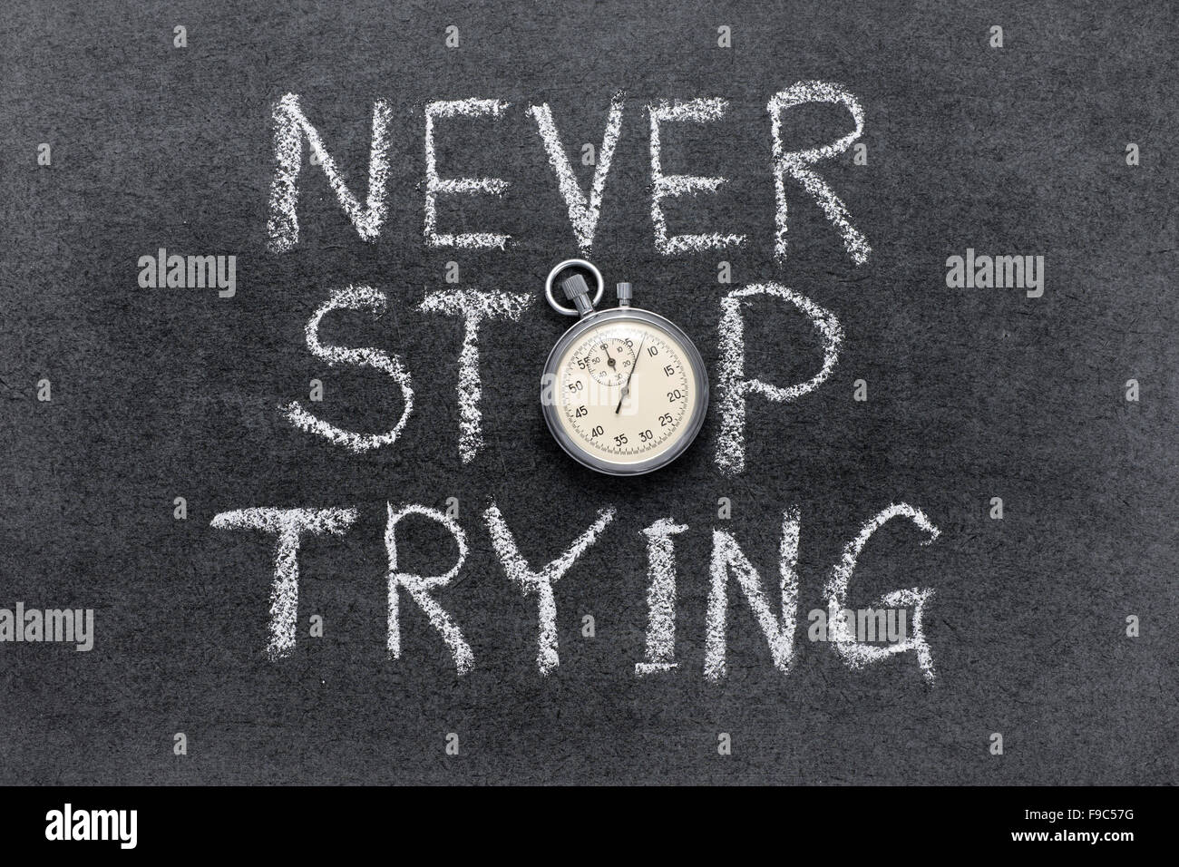 never stop trying phrase handwritten on chalkboard with vintage precise stopwatch used instead of O - Stock Image