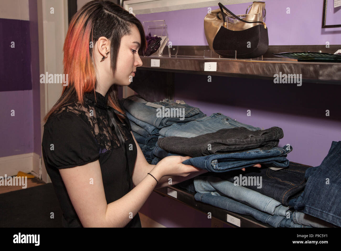 Teenage female clerk adjusting stack of jeans. Express Yourself Clothing Shop Trunk Show. St Paul Minnesota MN USA - Stock Image