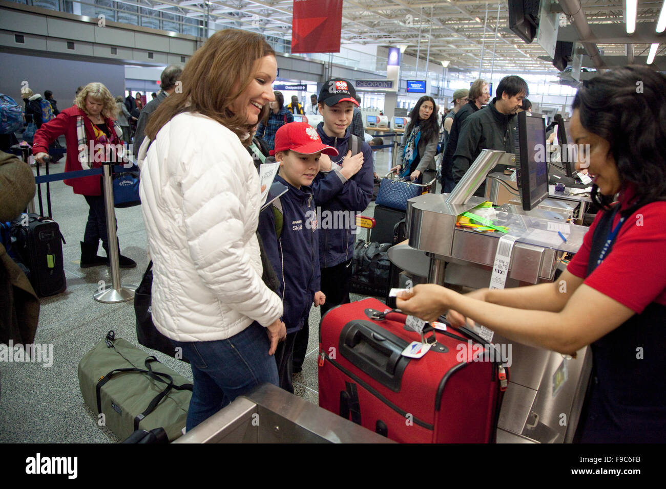 Mom and two sons watch Delta ticket agent attach ID tag on luggage at MSP International Airport. Minneapolis Minnesota - Stock Image