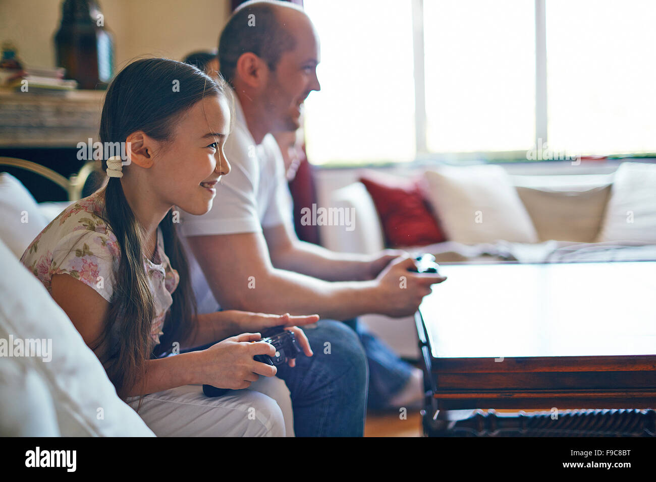 Smiling girl playing video games with her father - Stock Image