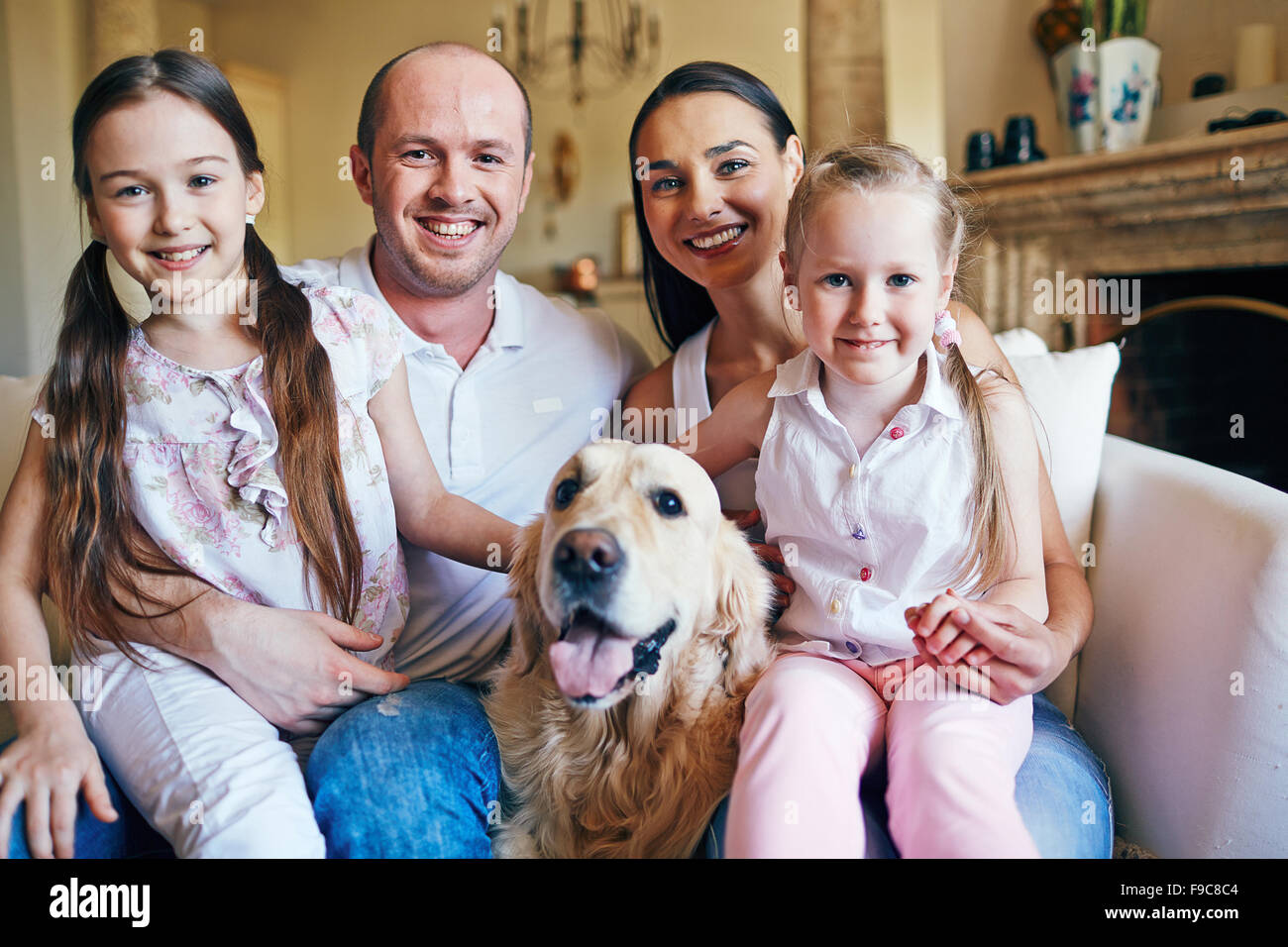 Portrait of happy family with dog - Stock Image