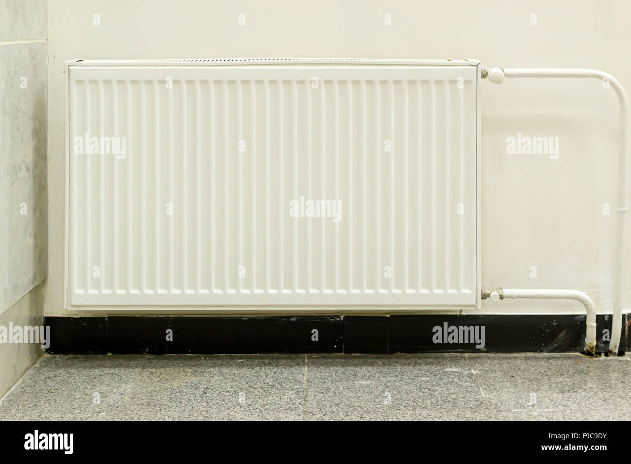 Single installed white residential radiator attached to a wall - Stock Image