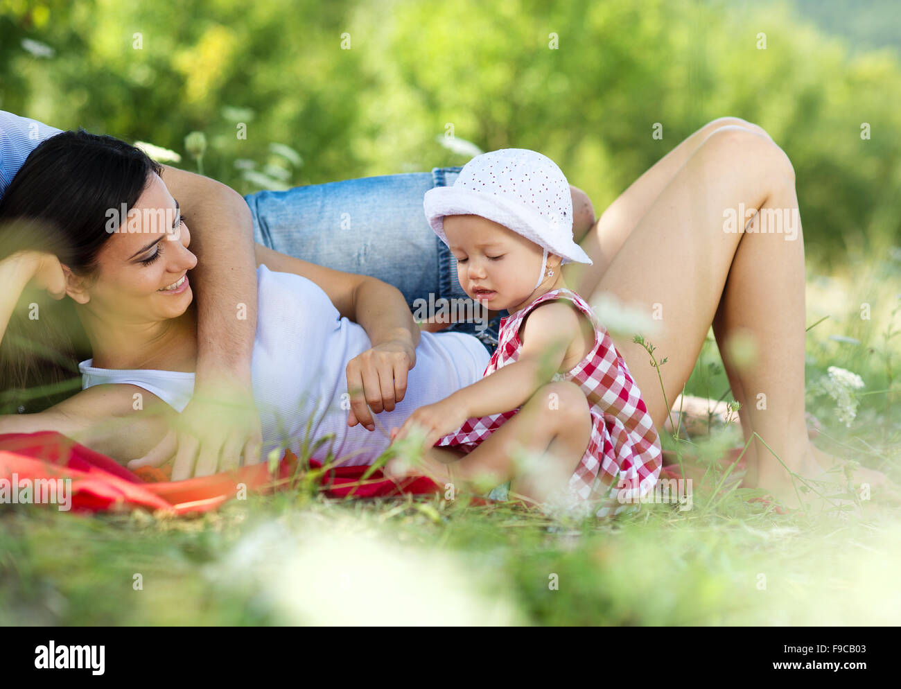 Happy young family spending time outdoor on a summer day - Stock Image