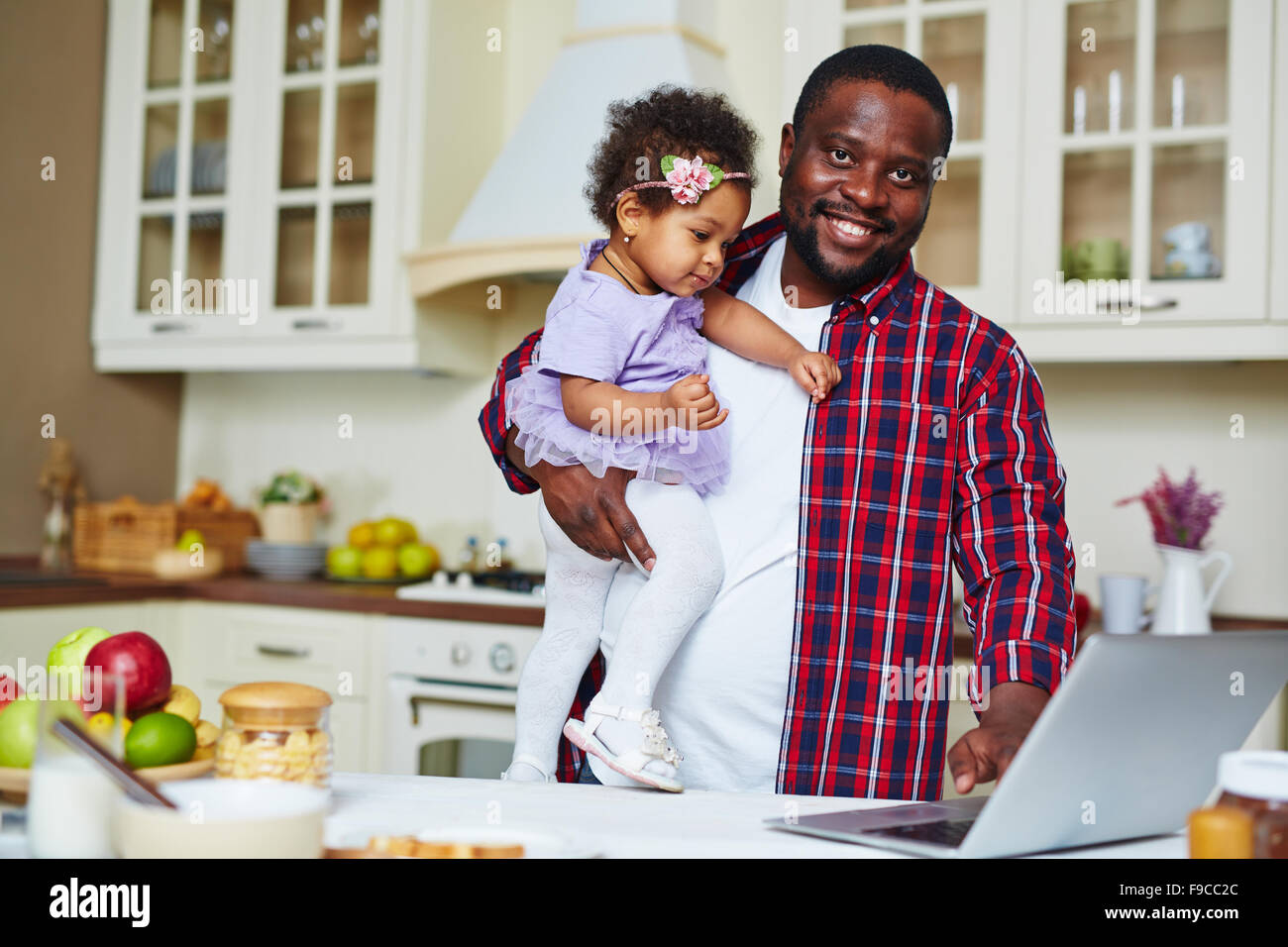 Young man with his small daughter networking in the kitchen - Stock Image