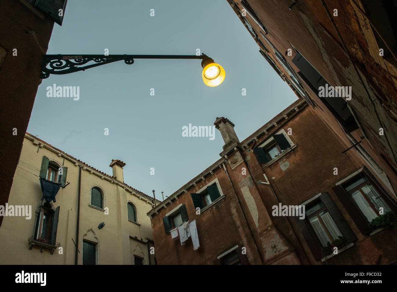 view upwards between the houses in Venice at sunset - Stock Image