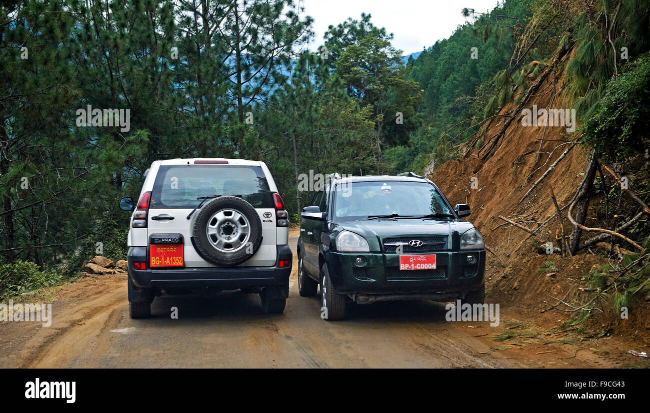 Two vehicles passing by each other narrowly on the Thimphu - Punakha Highway, Bhutan - Stock Image