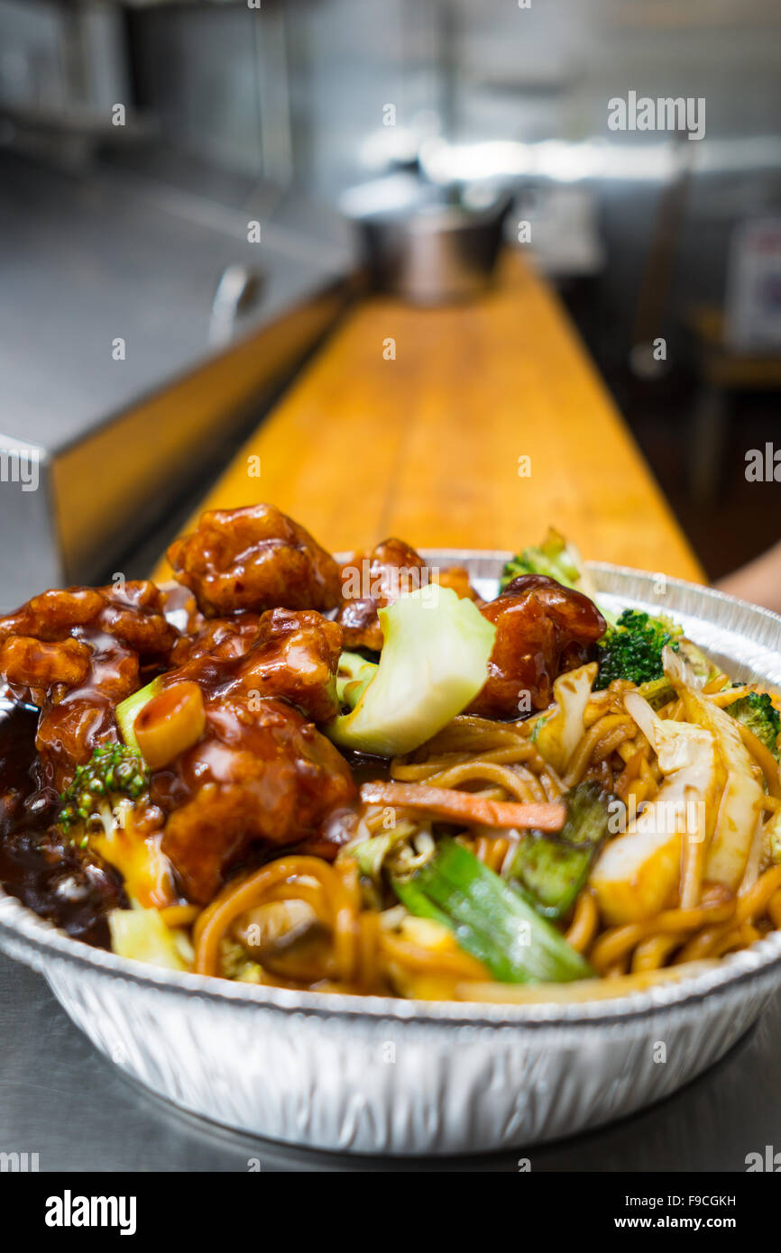 Chinese popular dish general tso's chicken on the kitchen table in  a take out foil container - Stock Image