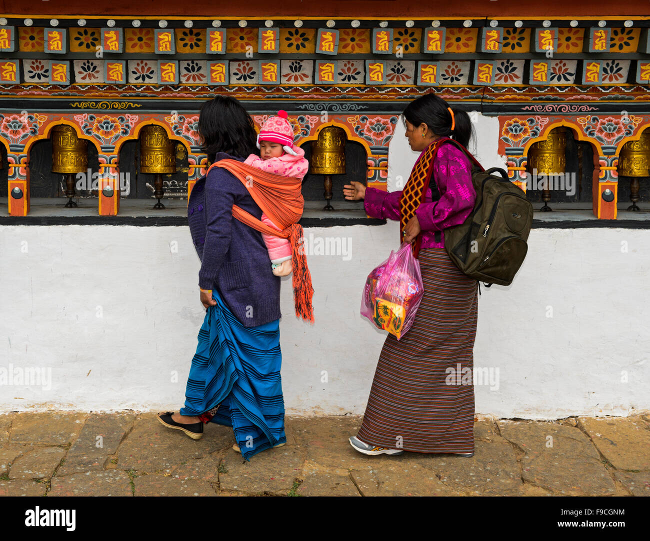 Two local women with a toddler on the back turning prayer mills, monastery Chime Lhakhang near Lobesa, Bhutan - Stock Image