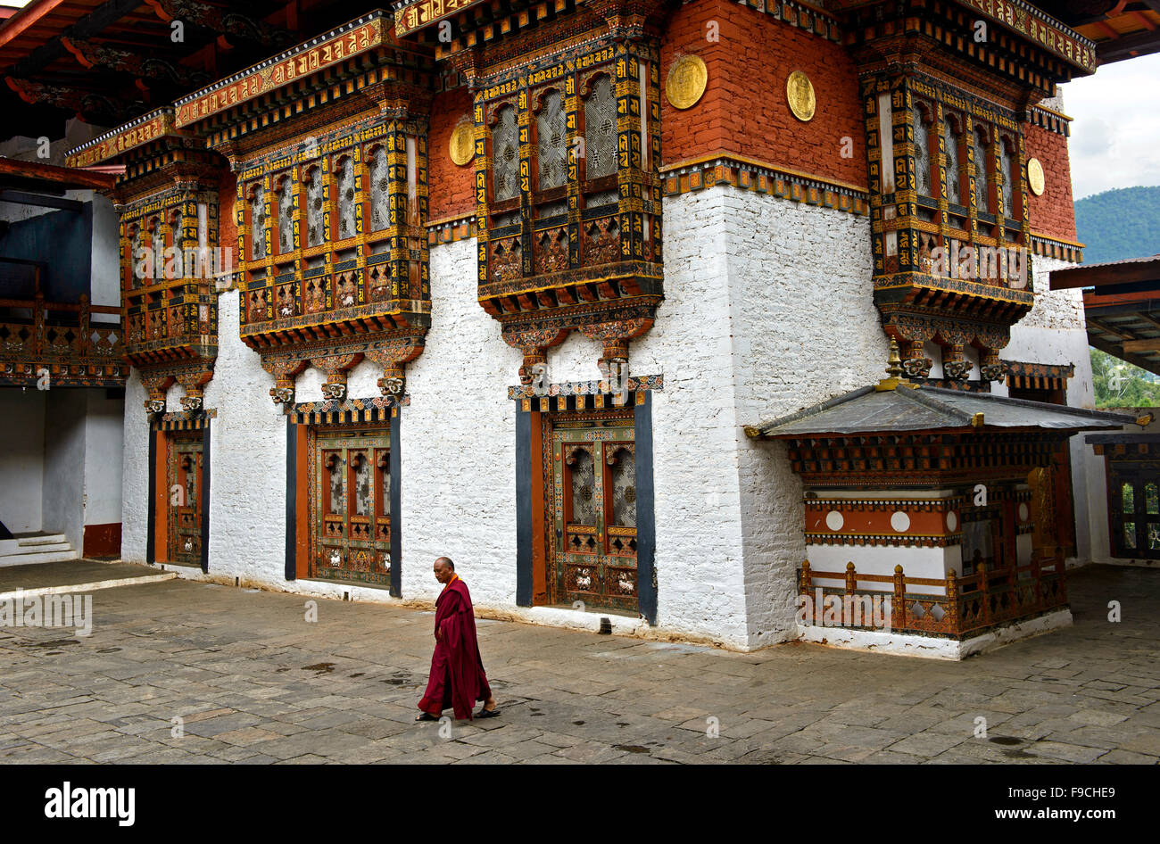 Buddhist monk striding through the courtyard of the monastery and fortress Punakha Dzong, Punakah, Bhutan - Stock Image