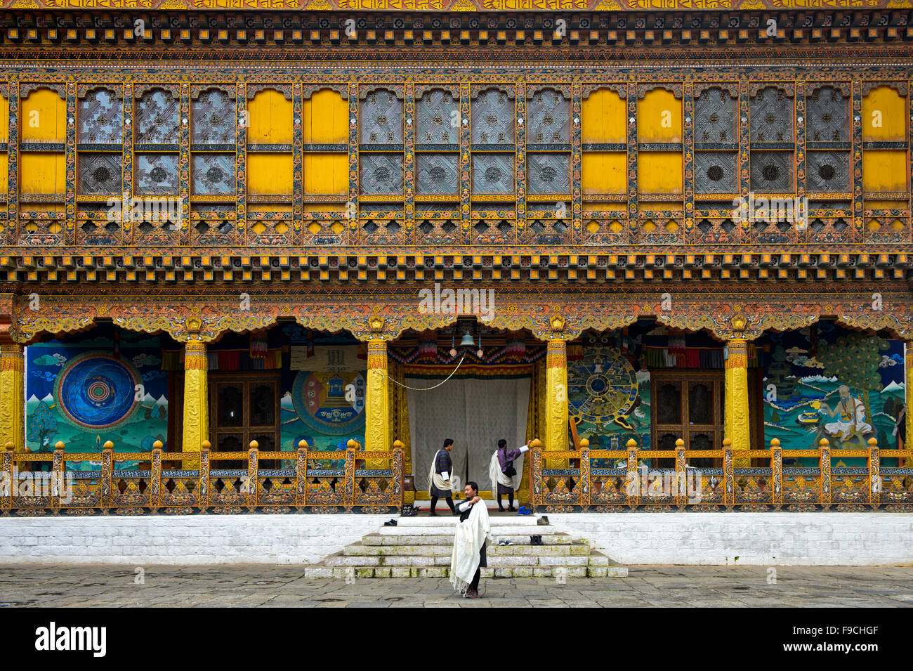 Three local men at the entrance to the coronation temple at the monastery and fortress Punakha Dzong, Punakah, Bhutan - Stock Image