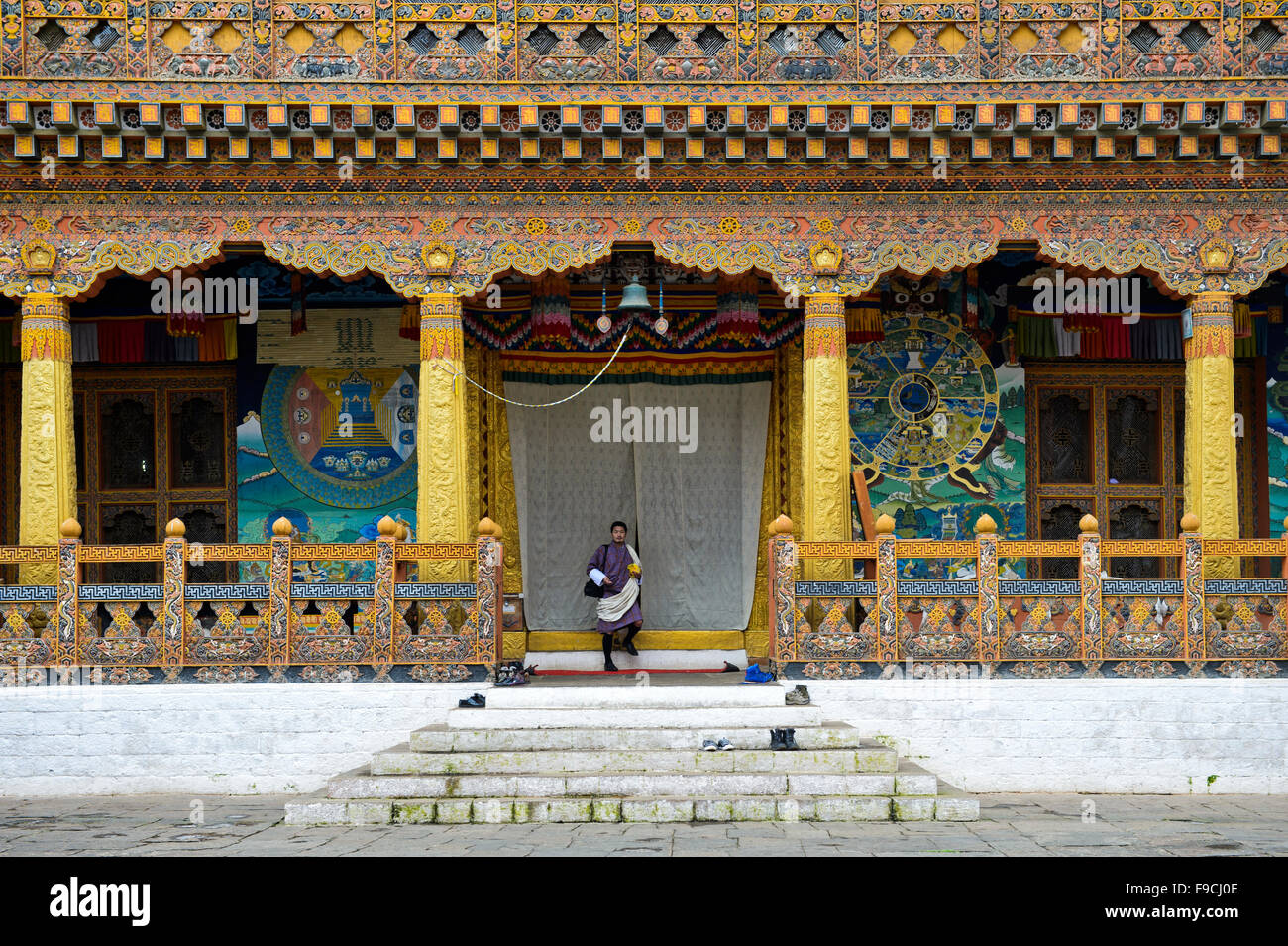 Local man at the entrance to the coronation temple at the monastery and fortress Punakha Dzong, Punakah, Bhutan - Stock Image