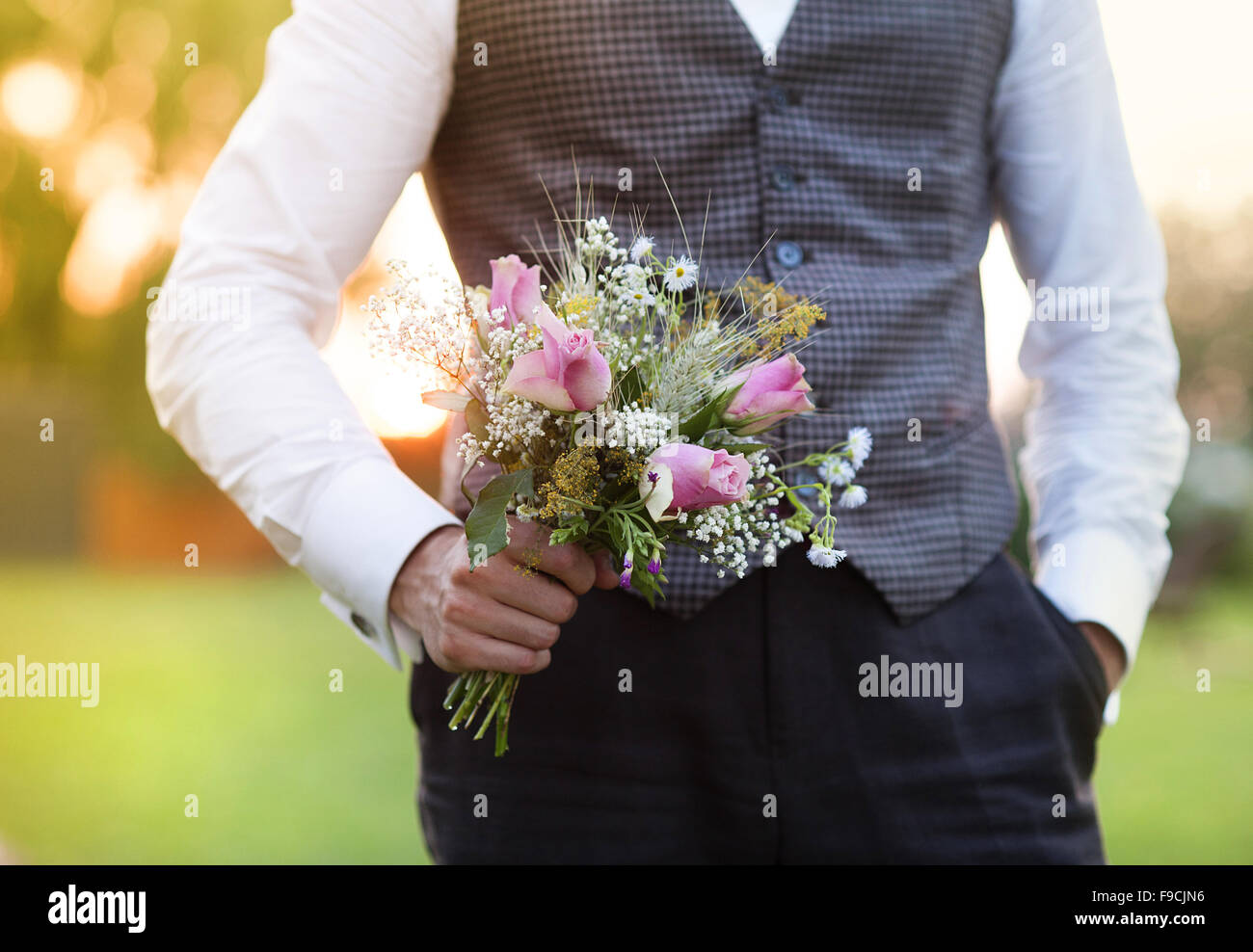 Part of the groom holding wedding bouquet in hand - Stock Image