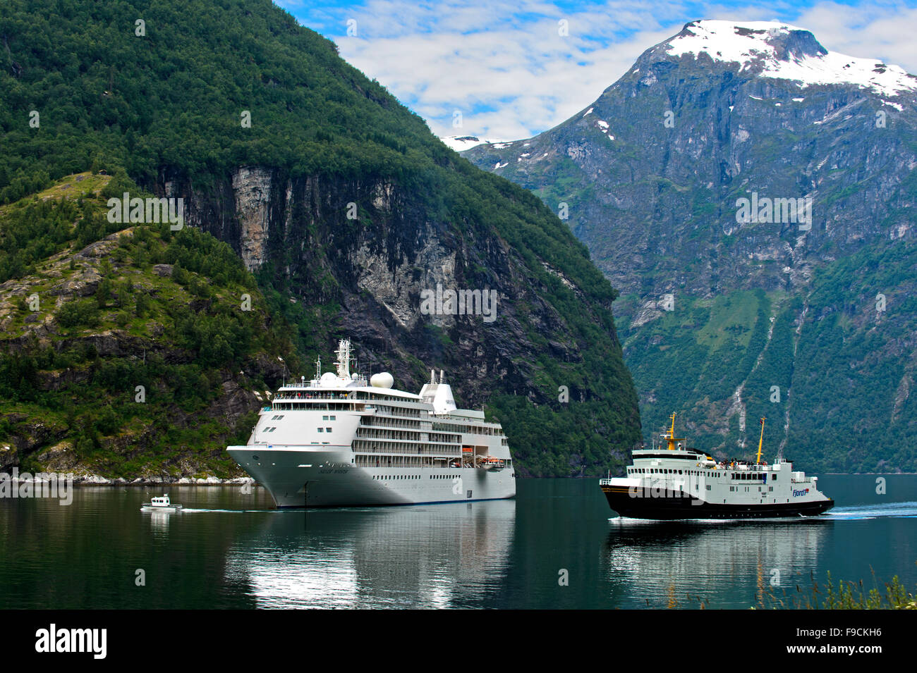 Cruise ship Silver Whisper and a local ferry in the Geirangerfjord, Geiranger, Norway - Stock Image