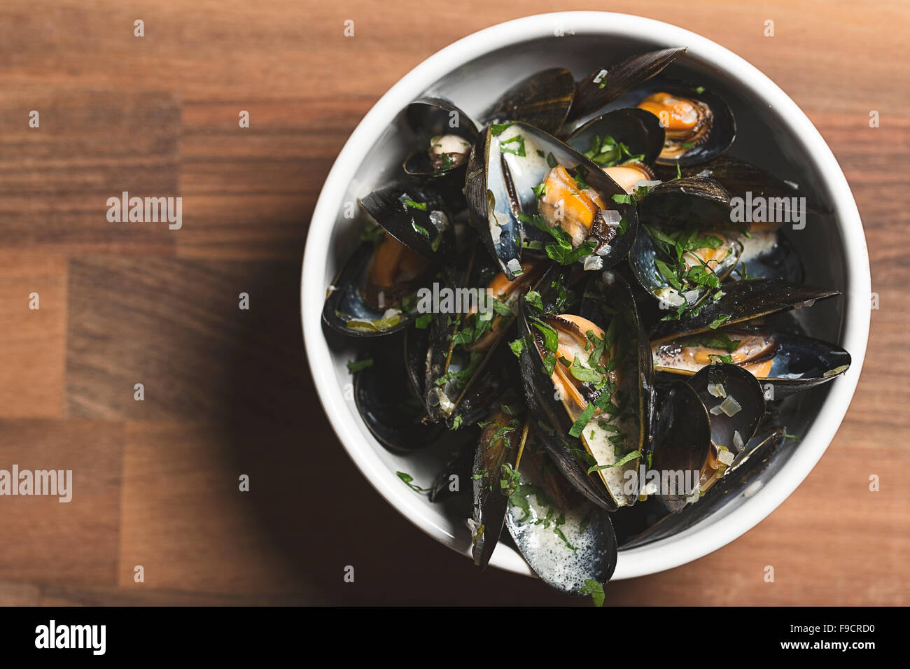 A bowl of cooked mussels in a white wine sauce - Stock Image