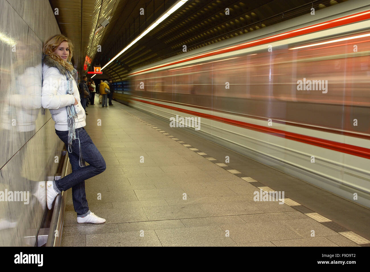 Girl Leant against Wall in Underground - Stock Image