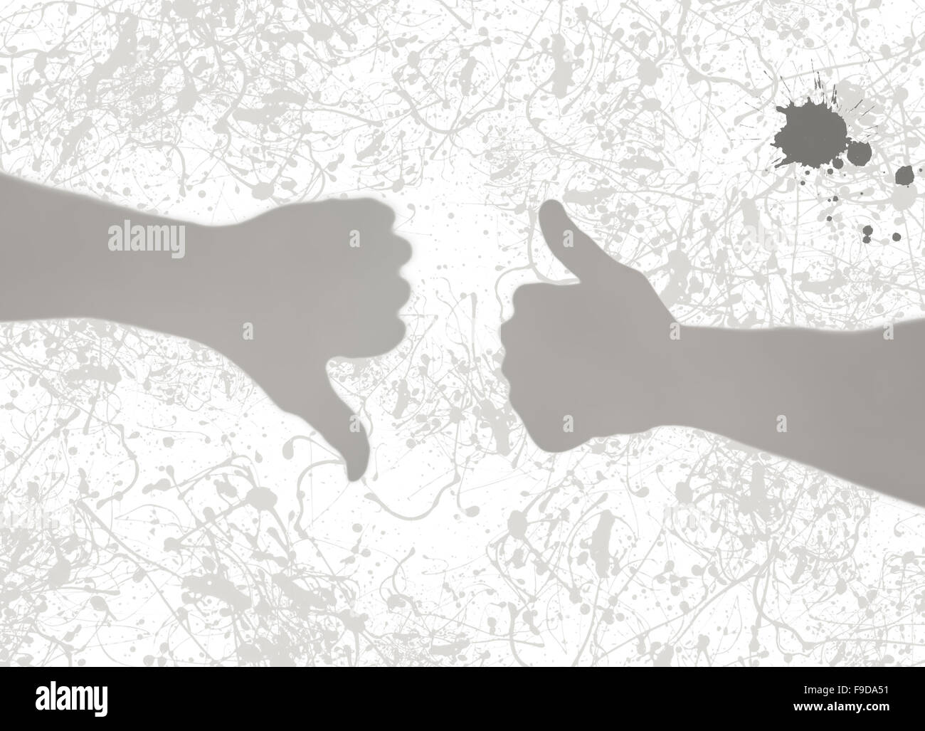 Gray shadows of two hands - thumbs up and thumbs down. Shadow play. - Stock Image