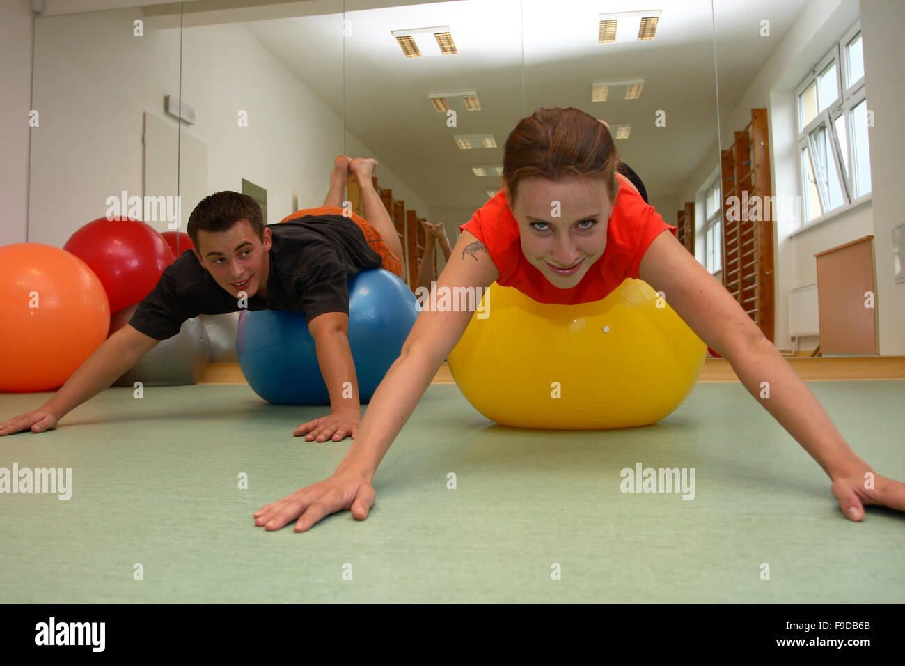 Young Couple Exercising On Fitness Balls - Stock Image