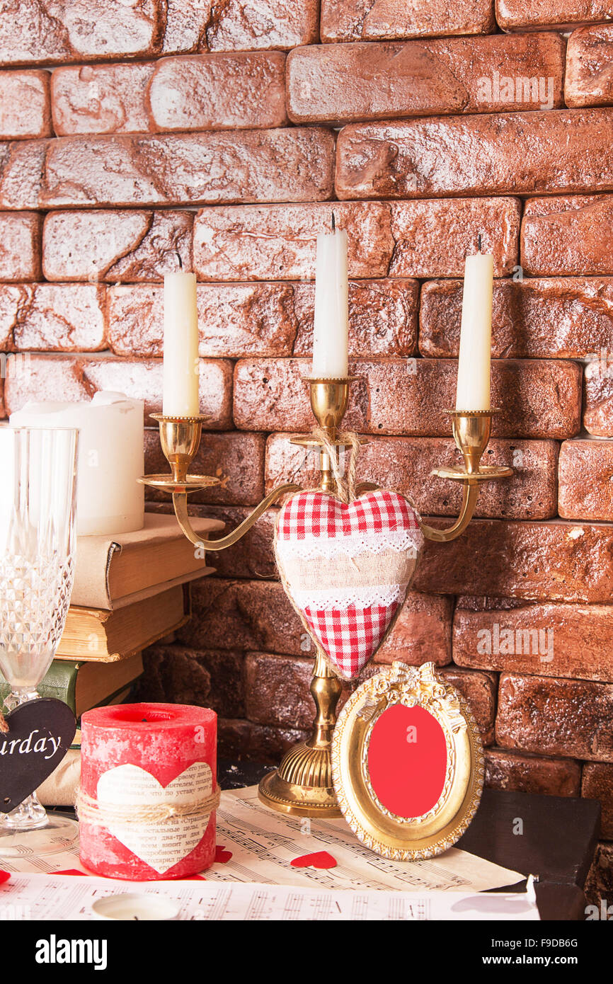 Golden Candlestick in the interior on the background of brown brick wall - Stock Image