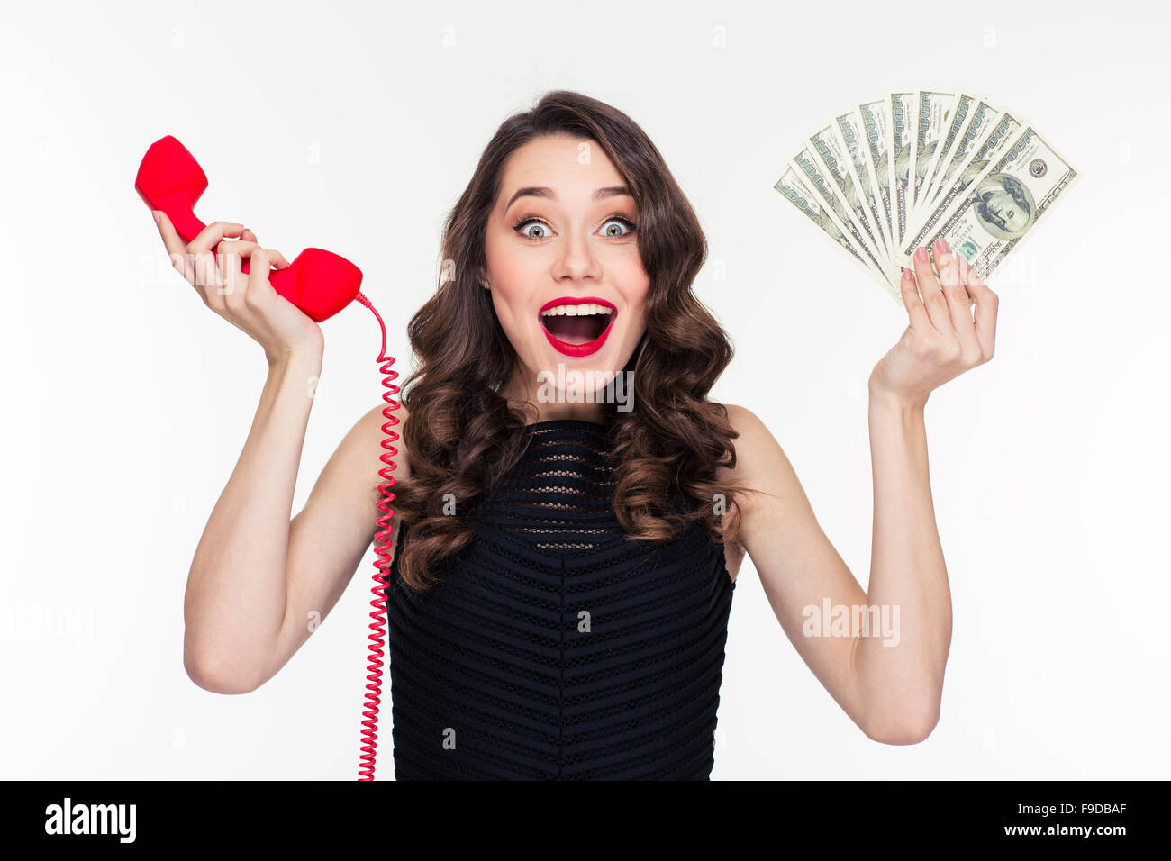 Beautiful excited happy young woman in retro style holding money and telephone receiver over white background Stock Photo