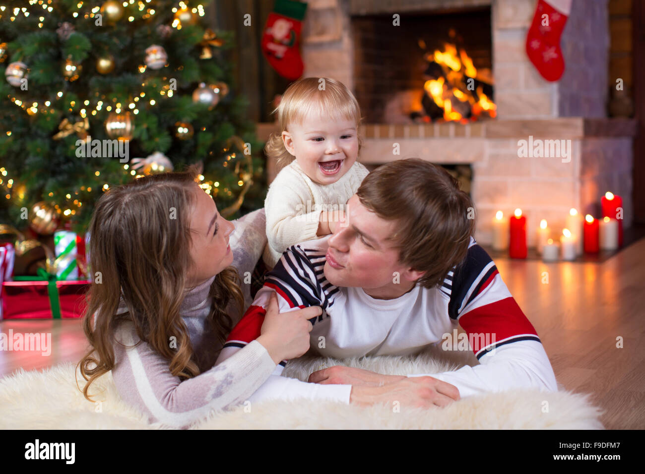 Happy young parents and child have a fun near Christmas tree at home.  Father, mother and son celebrating New Year - Stock Image